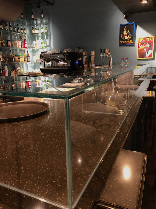 Il piano in cristallo extrachiaro del banco bar nel locale dolce casa
